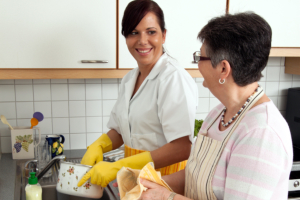 geriatric nurse with senior washing dishes in supervised living
