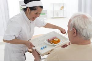 caregiver preparing breakfast to senior man
